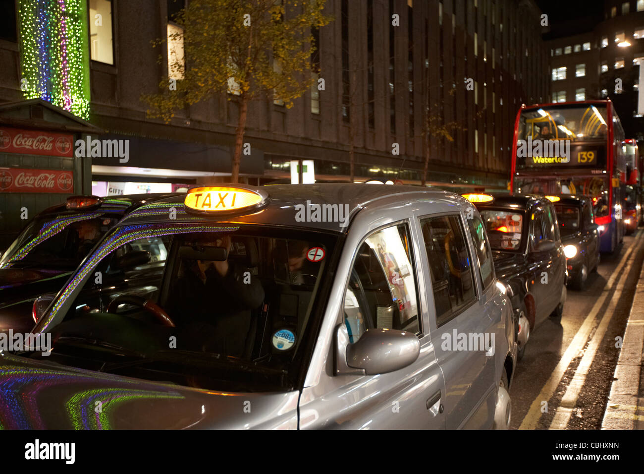 row of black london cabs taxis at night on shopping street in central london england united kingdom uk Stock Photo