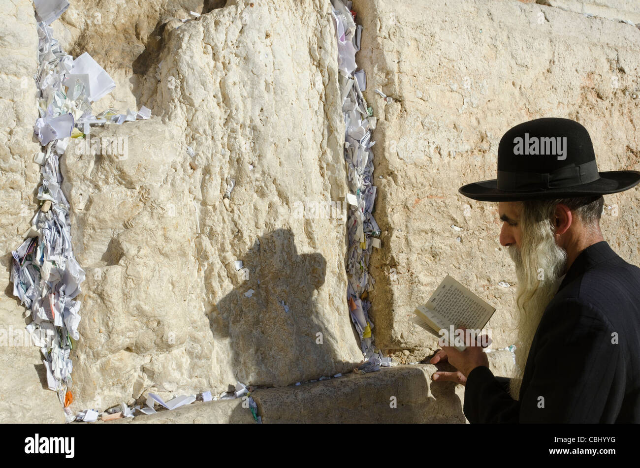 Orthodox Jew praying at Western Wall with paper notes in crack. Jerusalem Old City. Israel - Stock Image