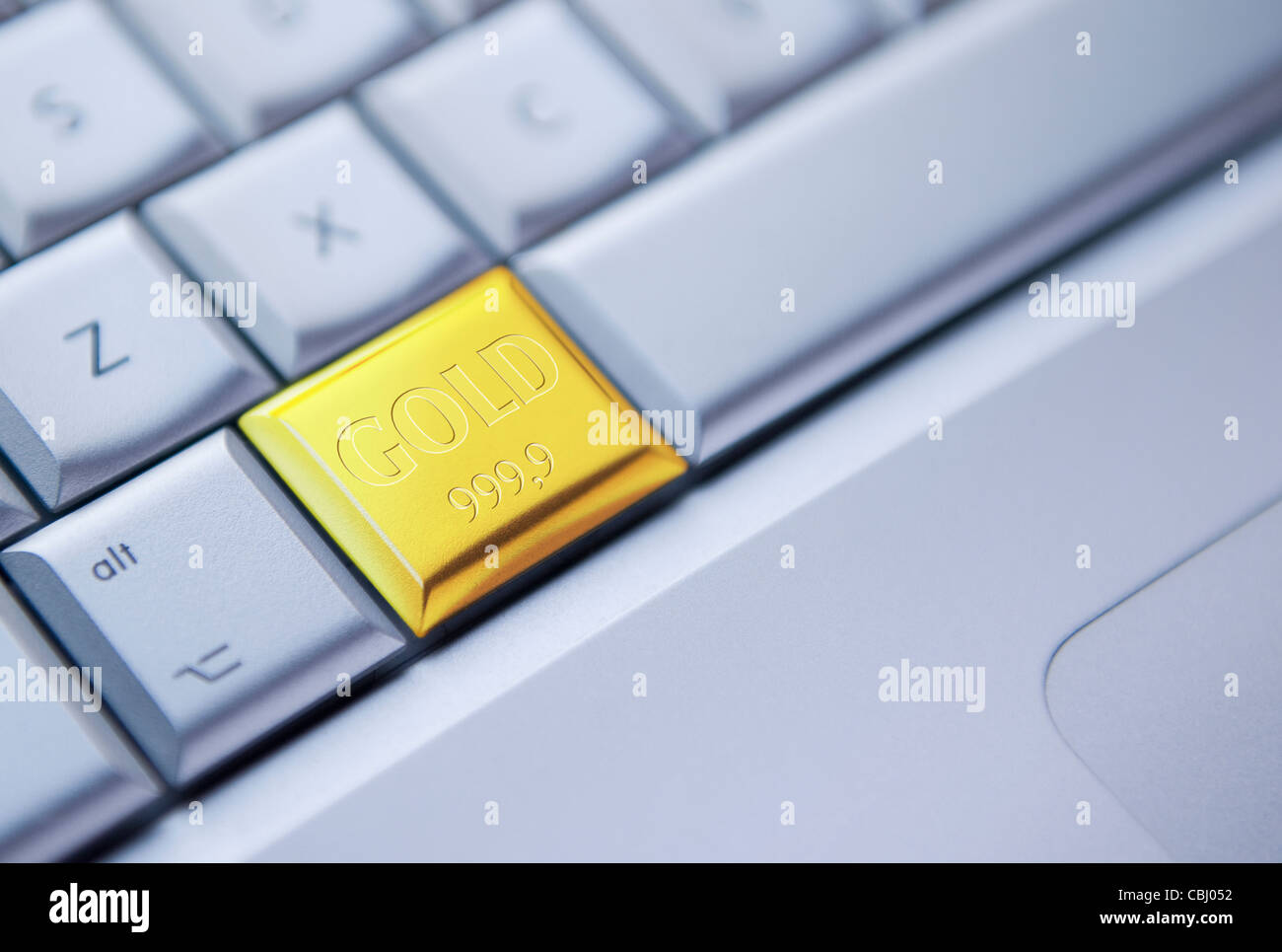 Detail of a keyboard with one key as a solid gold bar - Stock Image