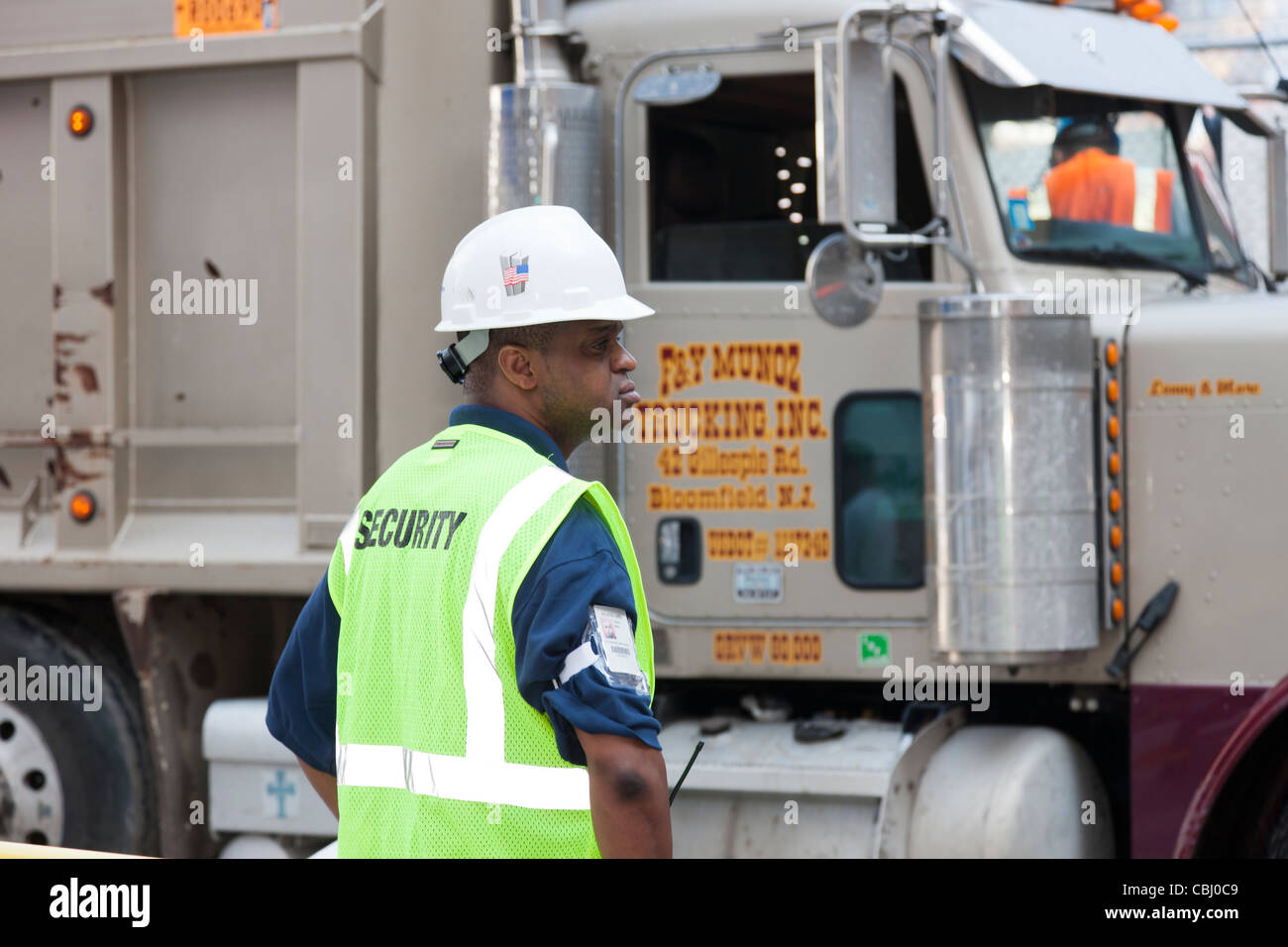 A security guard watches a dump truck exiting from the World Trade Center construction site in New York City. - Stock Image
