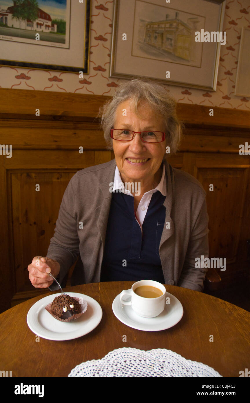 Female in her early 70s having coffee and cake Finland Europe - Stock Image