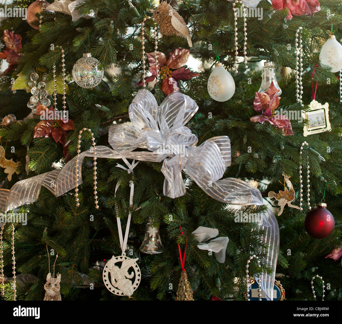 Christmas Tree Decorated With Silver And White Ribbons And Ornaments