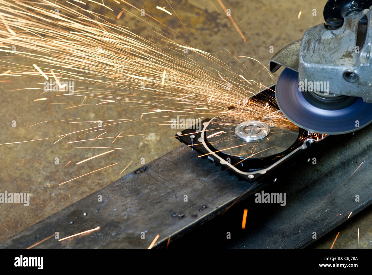 hard disk drive with rotating grinder and sparks in front of rusty back - Stock Image