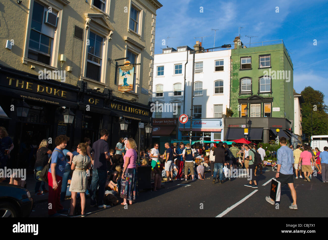 Corner of Elgin Crescent and Portobello Road streets on busy Saturday market day Notting Hill district London England - Stock Image