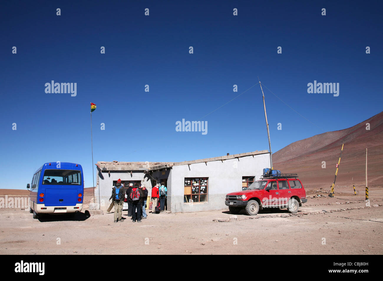 Four-wheel drive vehicles and tourists at official border post between Chile and Bolivia - Stock Image