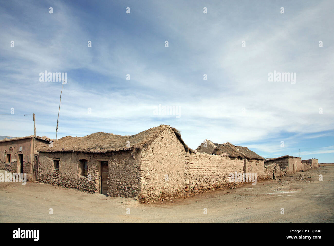 Street corner and adobe houses with thatched roofs in the village Colchani on the high plateau Altiplano, Bolivia - Stock Image