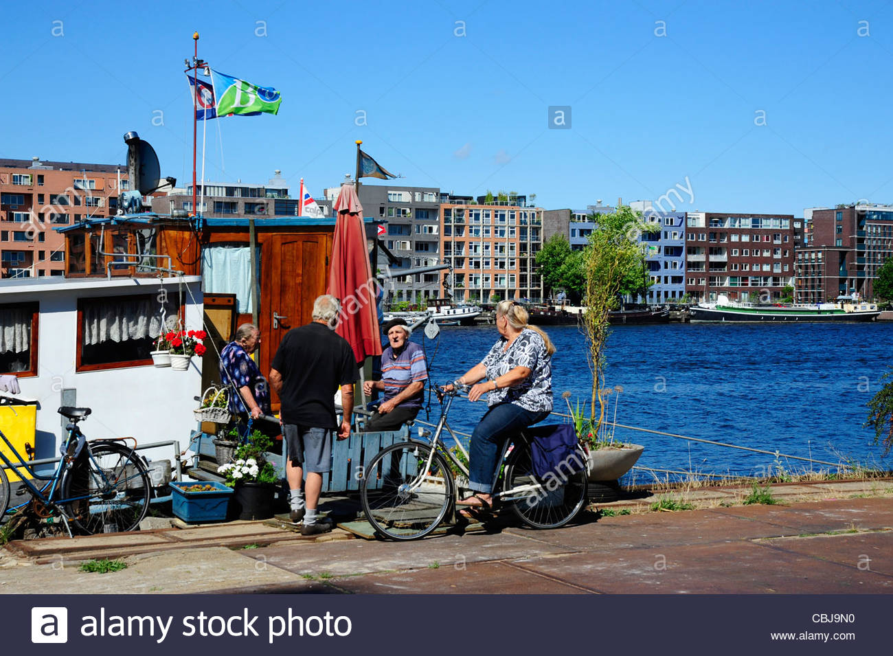 House boat at the Ijhaven canal, Veemkade, at back the island Java-Eiland, Amsterdam, the Netherlands, Europe - Stock Image