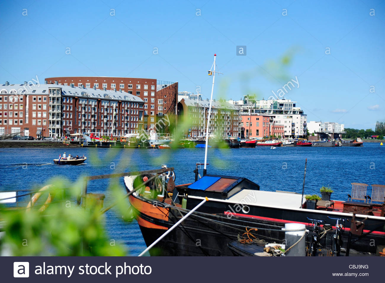 House boat at the Ijhaven canal, at back the island KNSM-Eiland, Amsterdam, the Netherlands, Europe - Stock Image