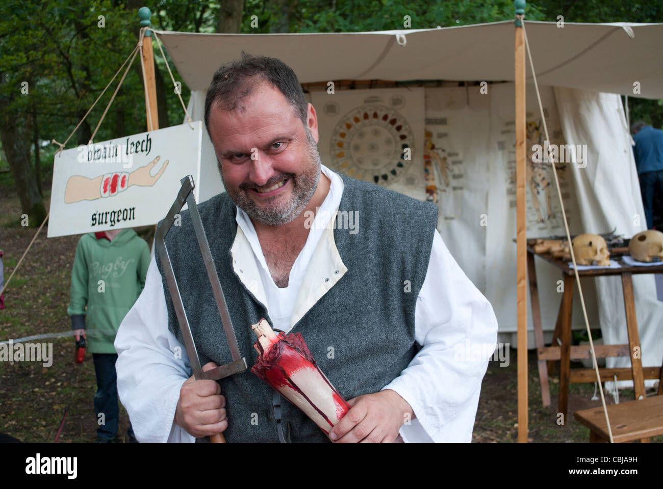 Man Dressed As Medieval Surgeon Wearing Bloody Apron Smiling And Holding Up Mock Severed Arm Saw At Robin Hood Festival