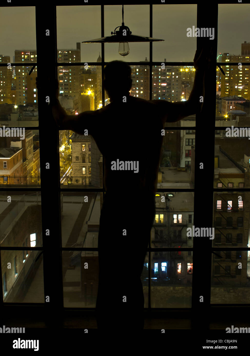 Silhouette of Man at window at night overlooking Nw York City, New York, USA - Stock Image