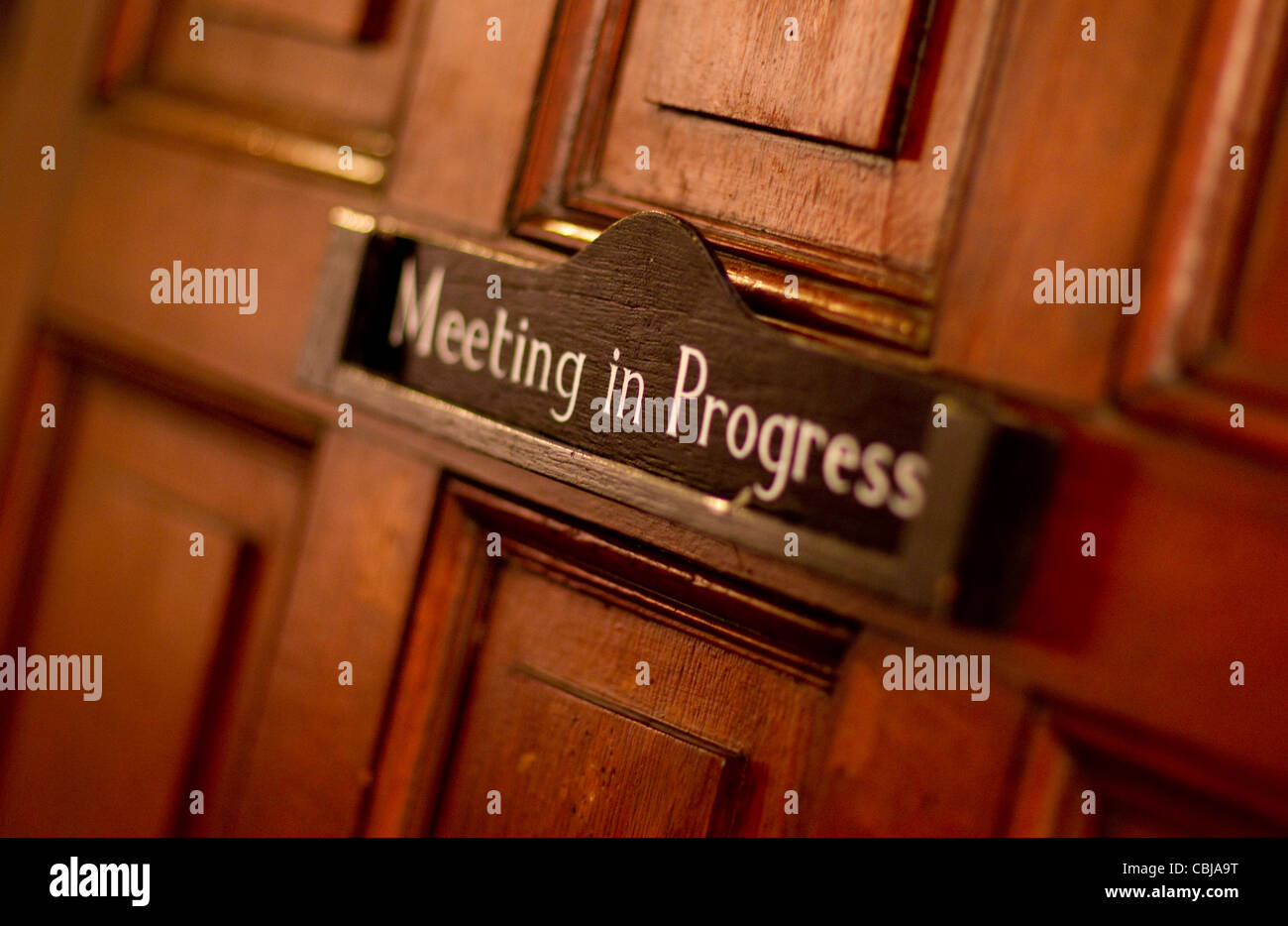 A door sign indicating that a meeting is in progress. - Stock Image
