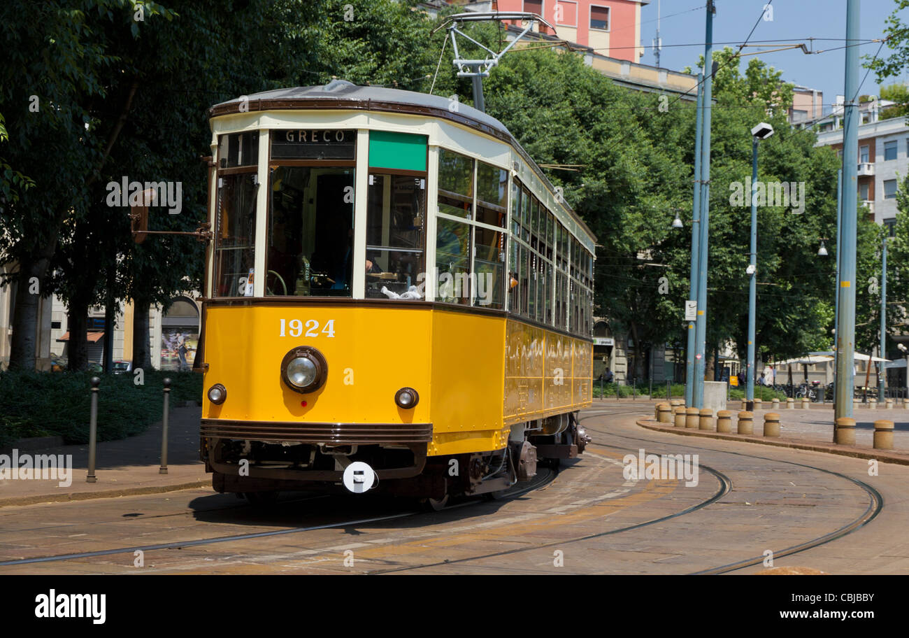 historic classic yellow tram of Milan on winding rails, Italy - Stock Image