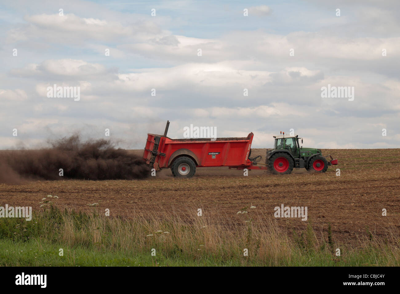 Tractor with Sodimac manure spreader (epandeur de fumier) spreading manure on an uncultivated field in northern - Stock Image