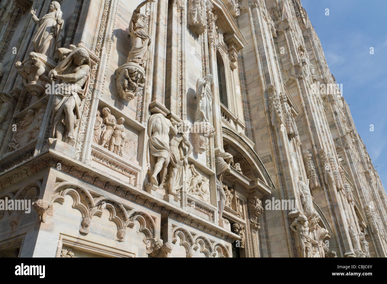 sculpted details of white marble and statues decorate the facade of cathedral duomo of Milan, Italy - Stock Image