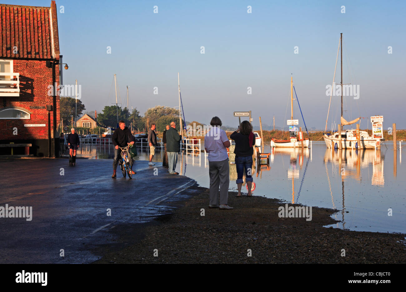 A group of onlookers observing a high spring tide at the quay at Blakeney, Norfolk, England, United Kingdom. - Stock Image