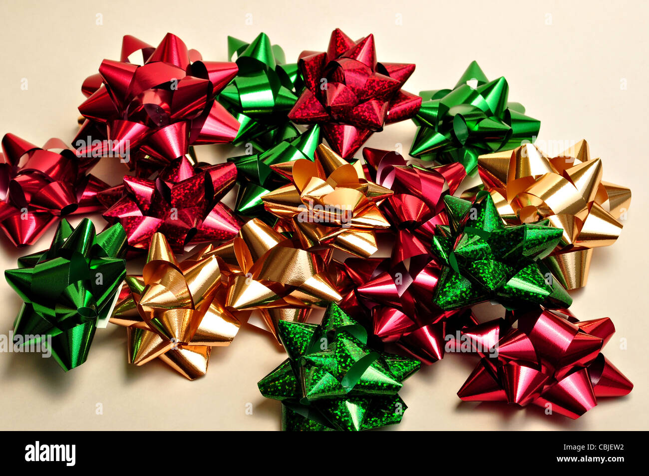 A bunch of Christmas bows lay on a white background. - Stock Image
