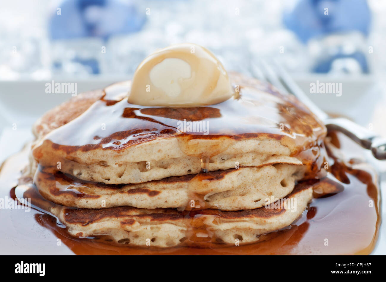 Fresh buttermilk pancakes with scoop of butter on white plate - Stock Image