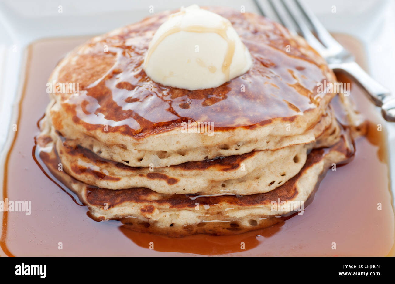 Fresh buttermilk pancakes with scoop of butter on white plate Stock Photo