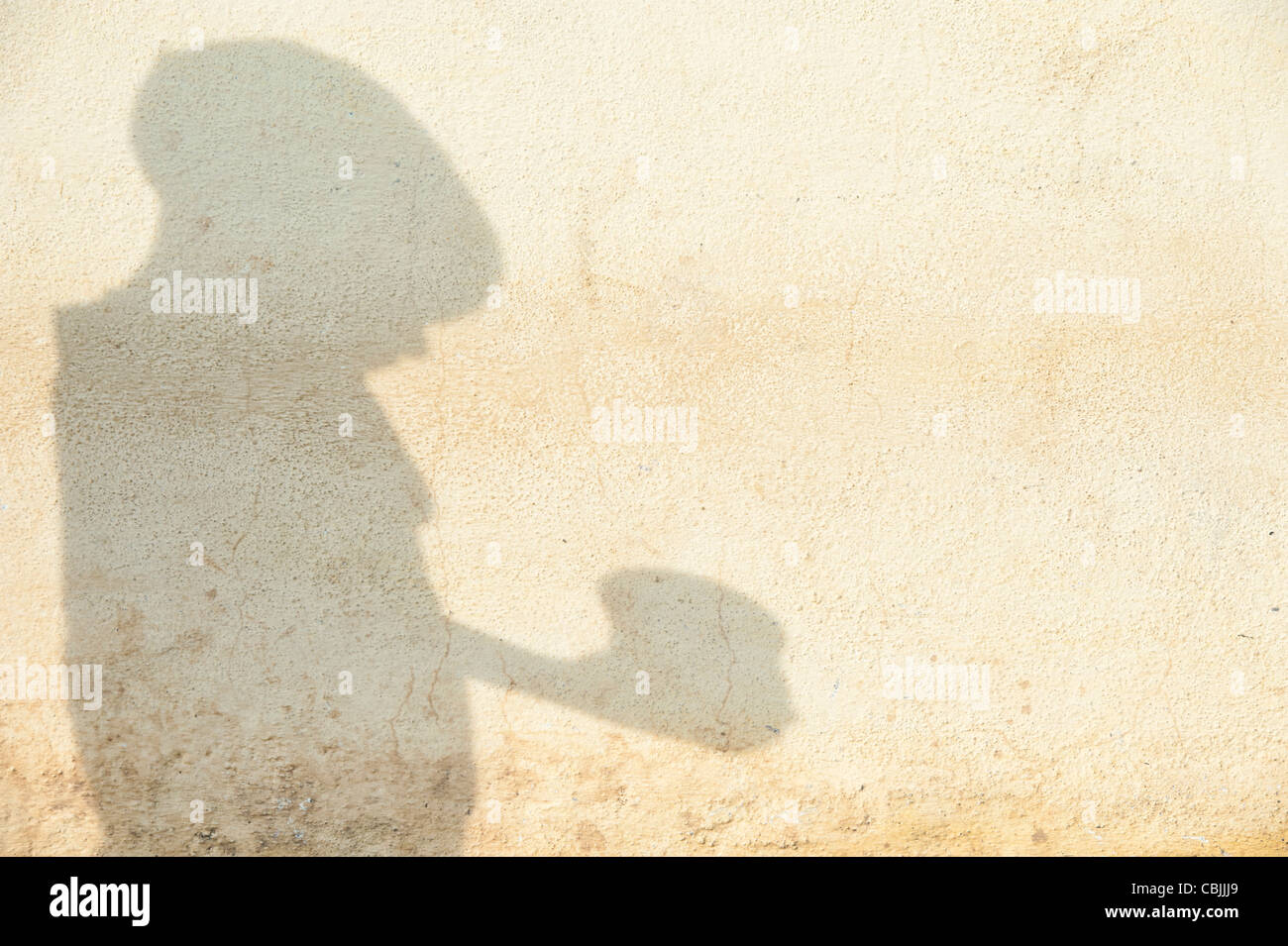 Shadow of a poor indian boy begging with a bowl - Stock Image