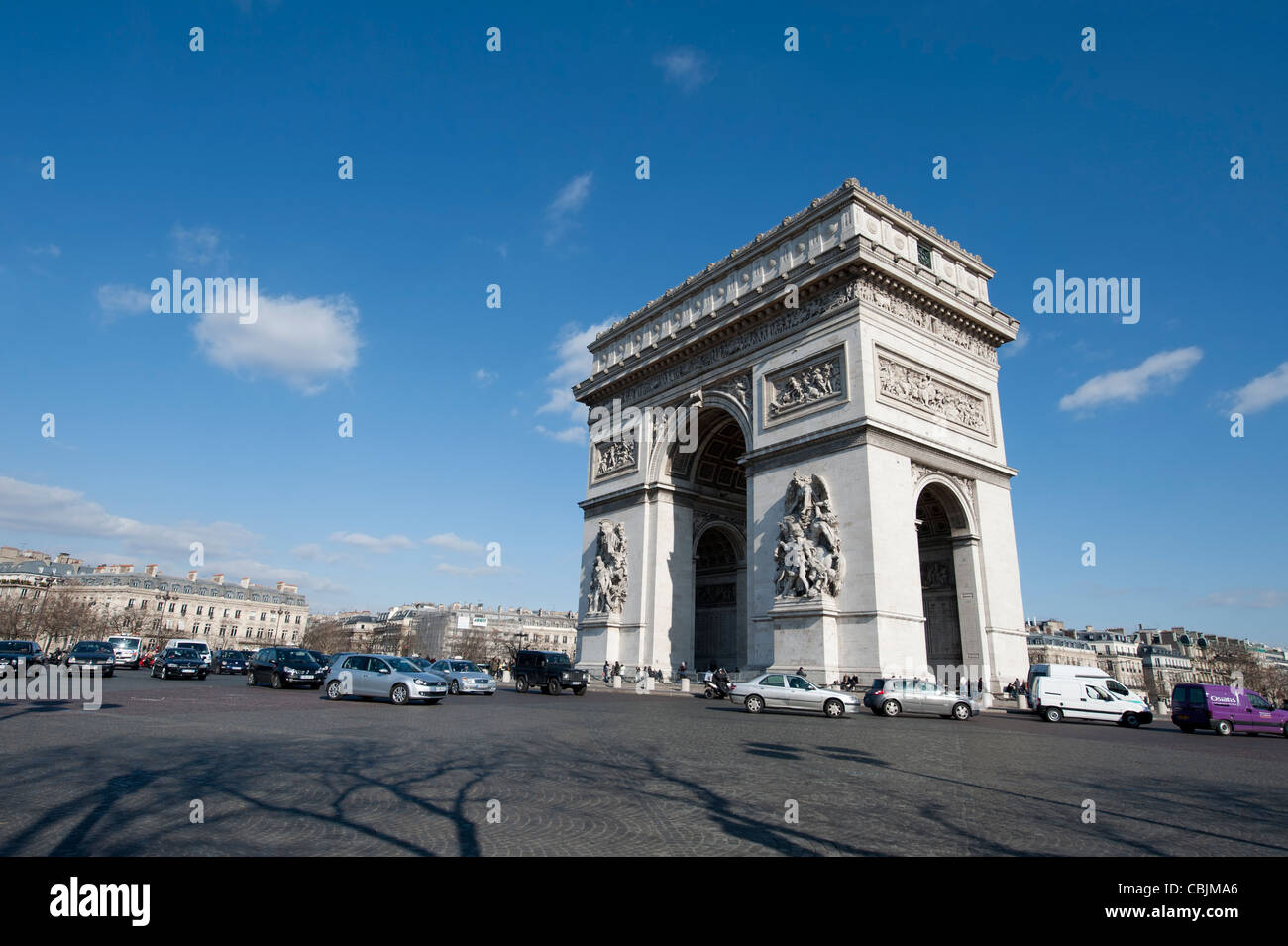 The Arc de Triomphe from the encompassing roundabout during the day time daytime featuring. - Stock Image