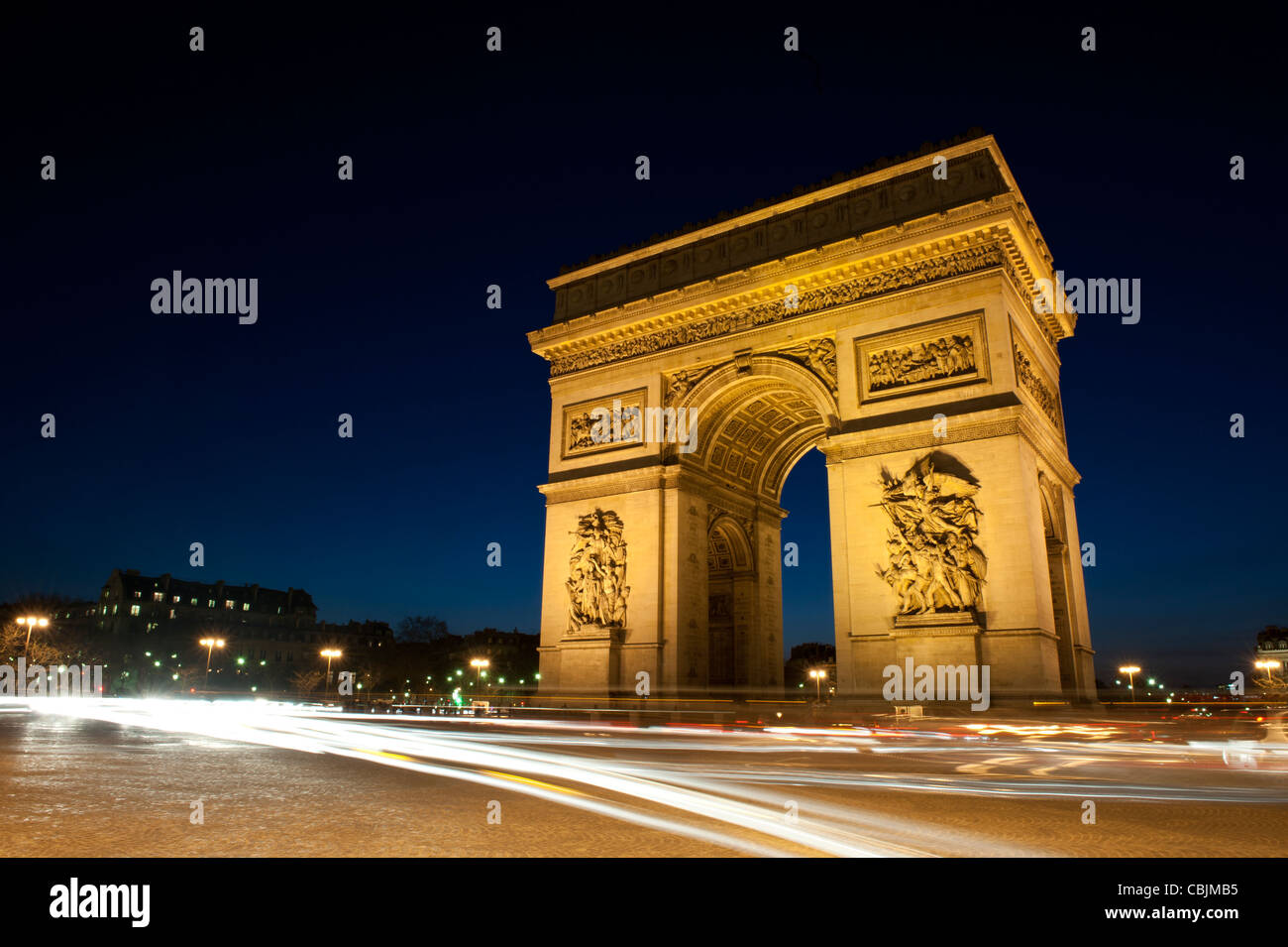 The Arc de Triomphe from the encompassing roundabout during evening, featuring light trails from traffic. - Stock Image