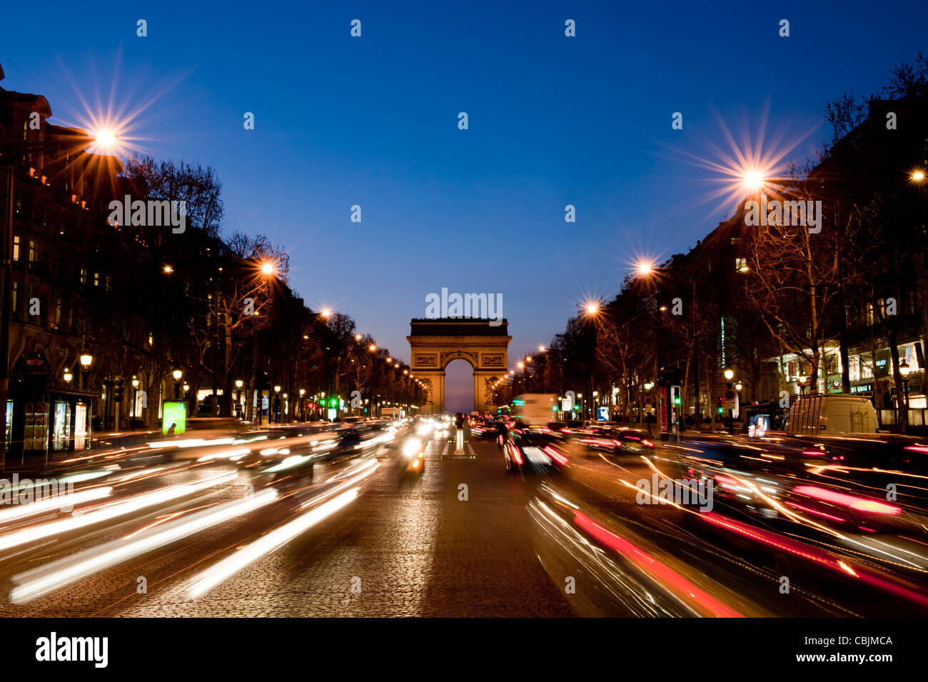 A wide-angle view Arc de Triomphe from Champs Elysees during evening, featuring light trails from traffic. - Stock Image