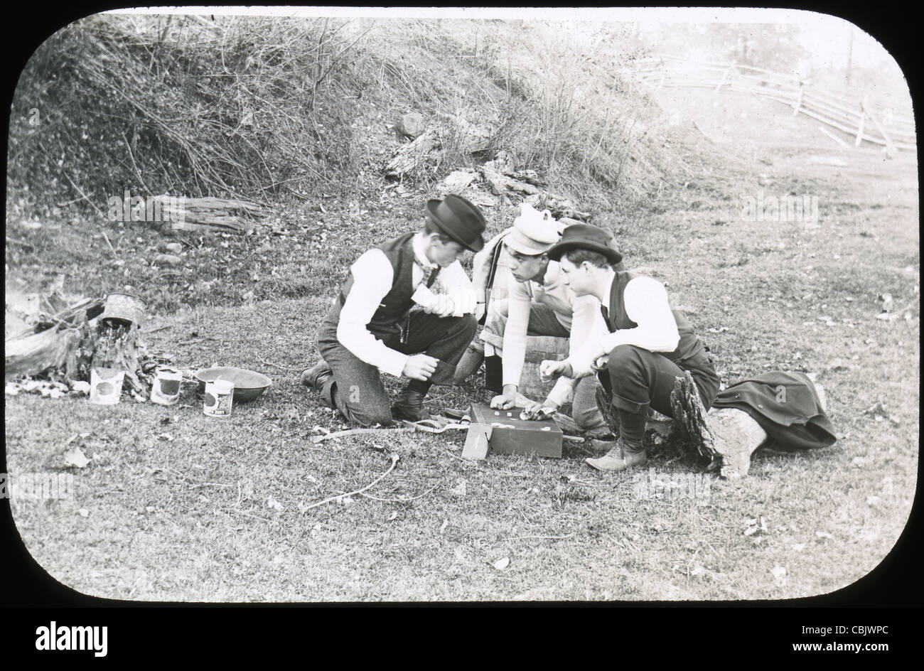 Circa 1910s antique photograph of three men wagering on some sort of dice game. - Stock Image