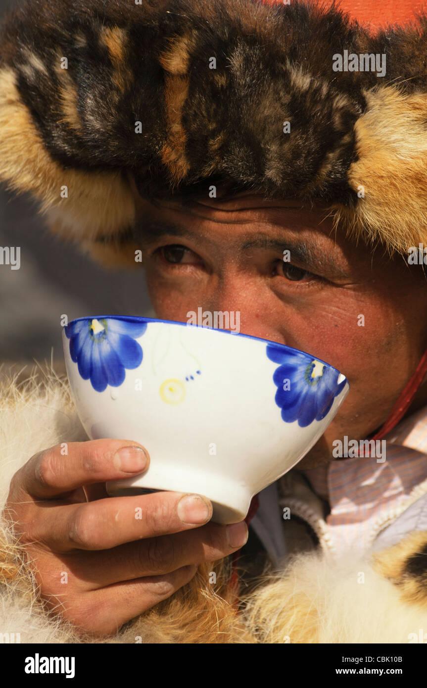 Kazakh eagle hunter drinking milk tea in the Altai Region of Bayan-Ölgii in Western Mongolia Stock Photo