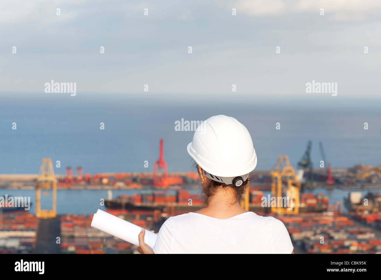 Female latin engineer with a plan looking at a harbour - Stock Image