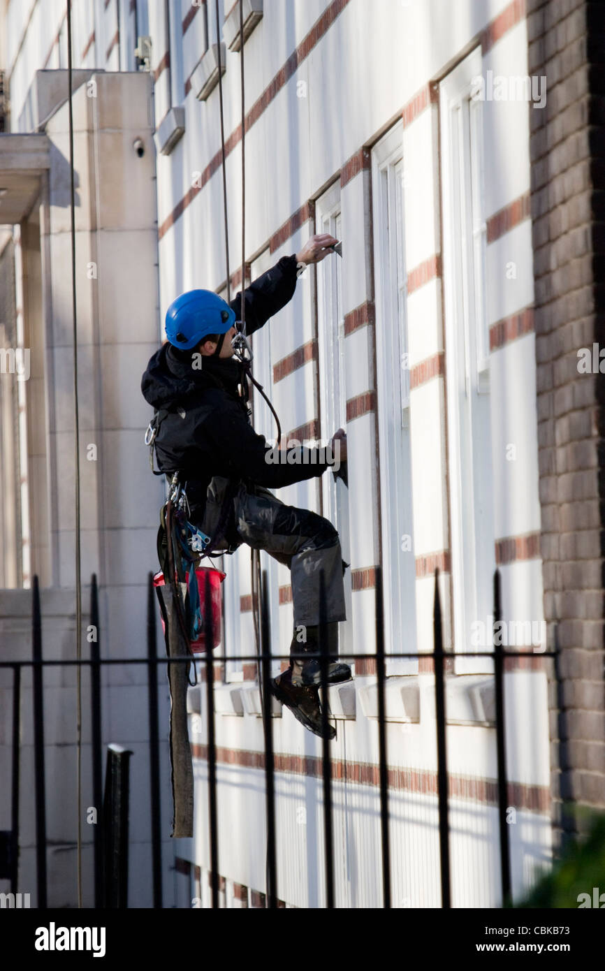 roped access technician, abseiling window cleaner - Stock Image