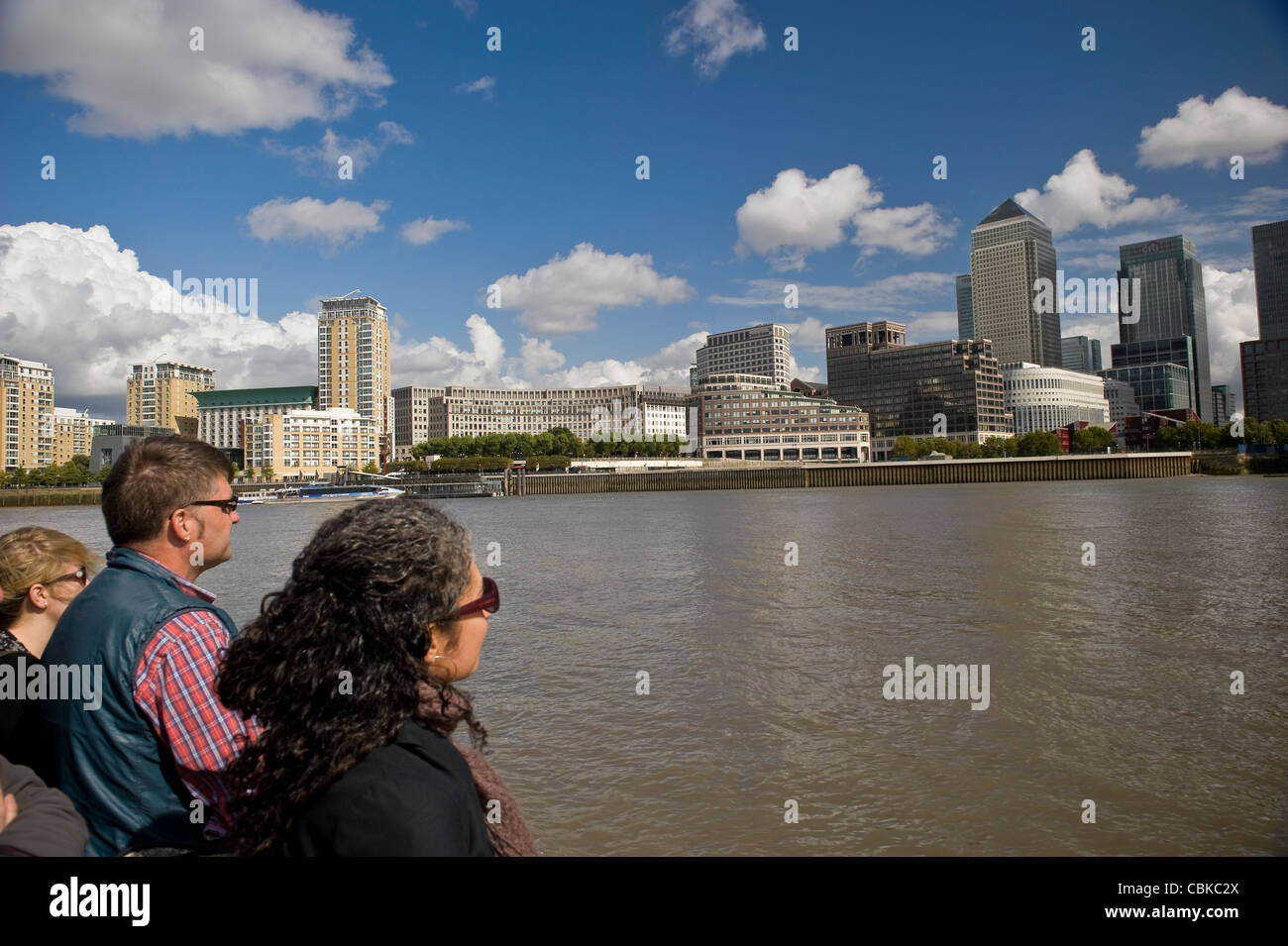 Sightseers on a Thames River boat guided tour viewing Docklands Canary Wharf, London, UK - Stock Image