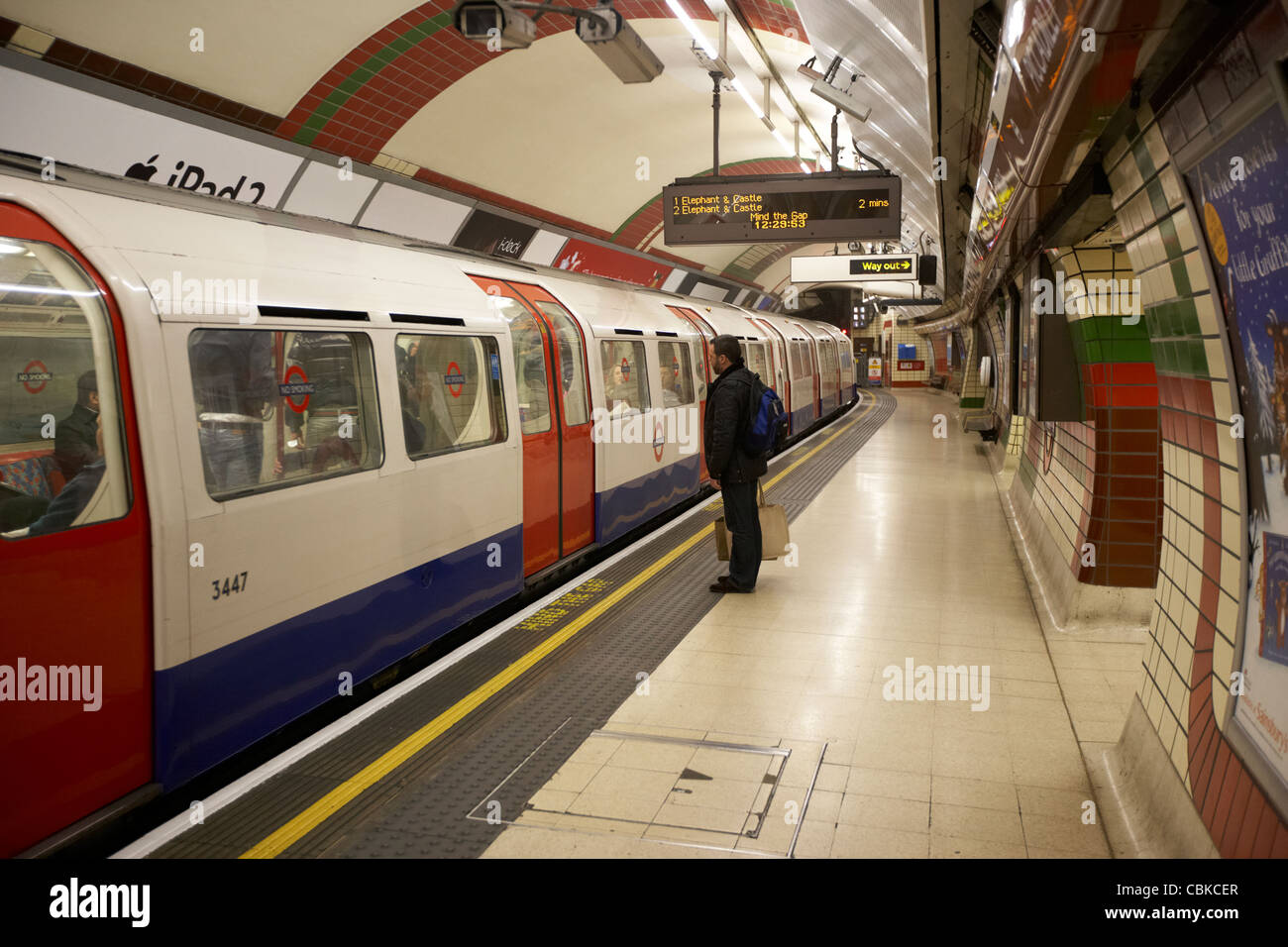 london underground train arriving in piccadilly circus station with single male passenger waiting england united - Stock Image