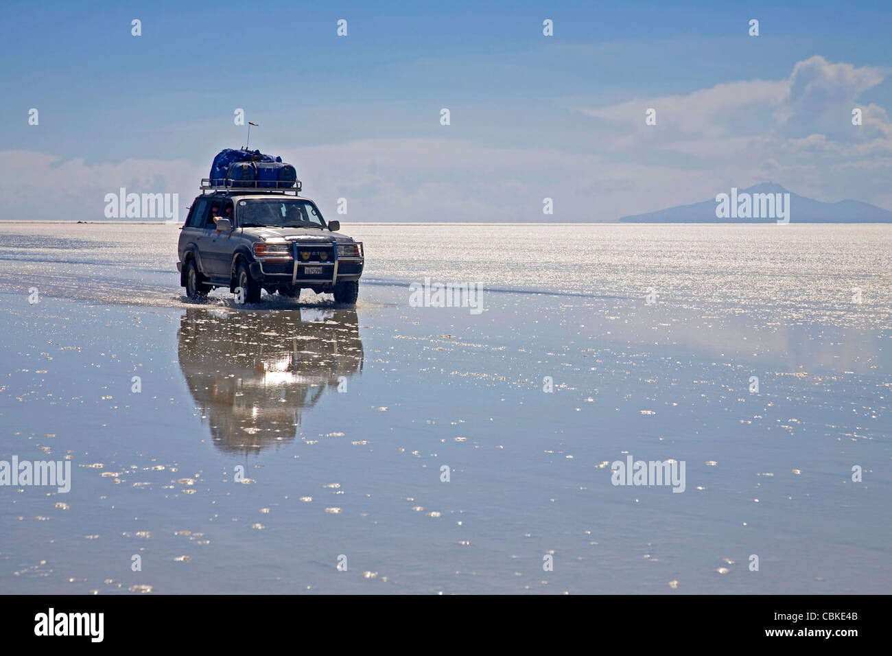 Four-wheel drive vehicle driving on the salt flat Salar de Uyuni, Altiplano in Bolivia - Stock Image