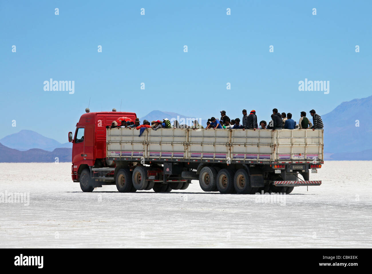 Truck with school children on the salt flat Salar de Uyuni, Altiplano, Bolivia - Stock Image