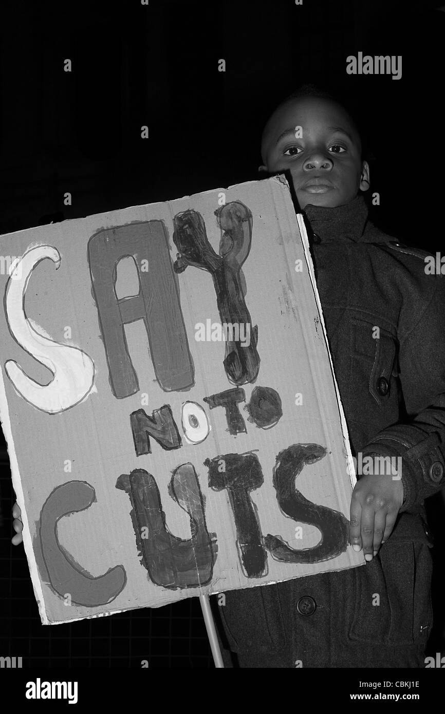 "Young black boy holds a placard that reads ""Say no to cuts"". Stock Photo"
