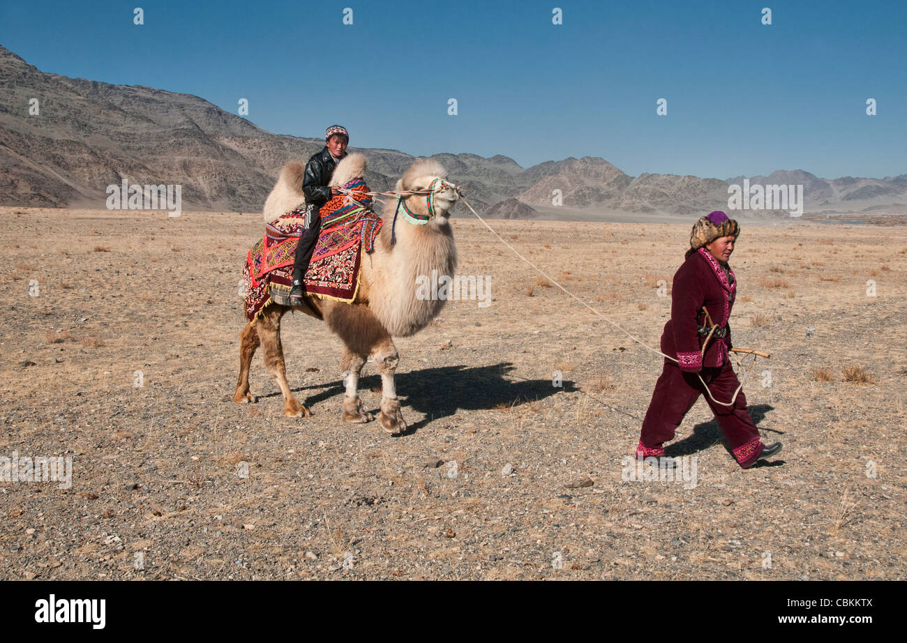 Kazakh man and his Bactrian camel on the Central Asian Steppe at the Kazakh Eagle Hunters' Festival in Bayan-Ölgii, Stock Photo