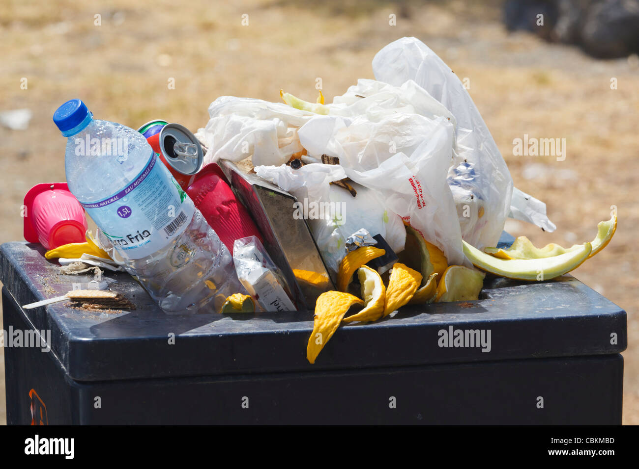 Overflowing rubbish bin at highway rest stop, southern Spain. - Stock Image