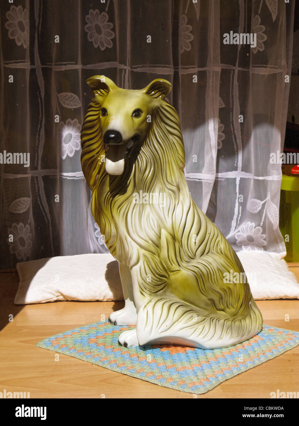 Kitsch retro pottery dog statue in a window - Stock Image