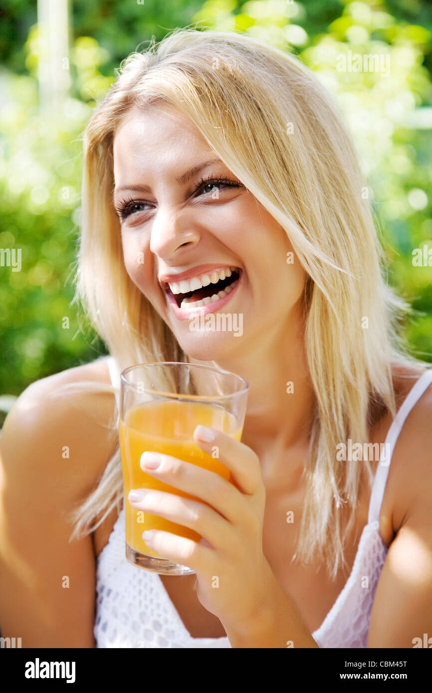 happy woman drinking her morning orange juice in her garden - Stock Image