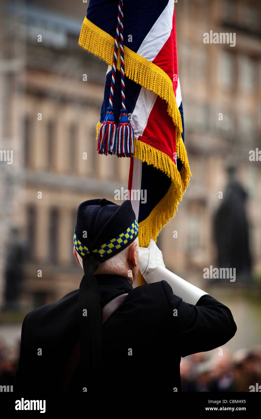 Retired soldier holding a flag at the annual Remembrance Service, George Square, Glasgow, Scotland, UK, Great Britain - Stock Image