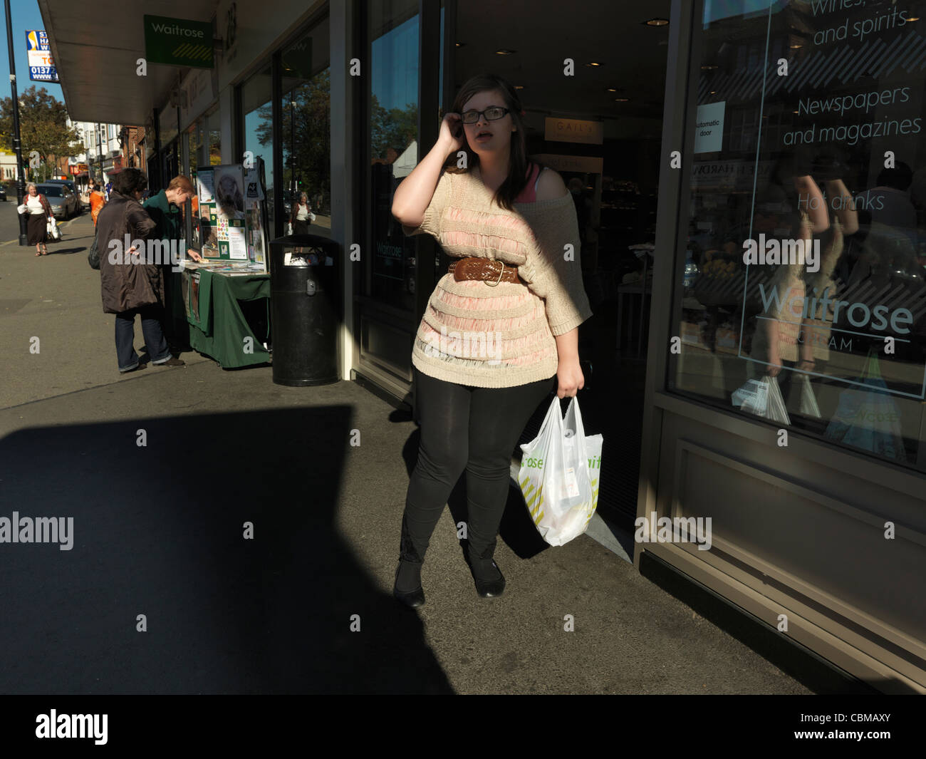 Woman Coming Out Of Waitrose Supermarket Carrying Food In Plastic Recyclable Shopping Bag Cheam Village England - Stock Image