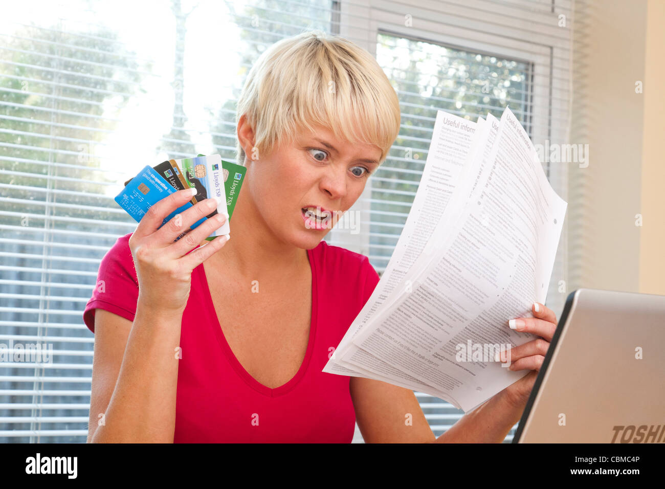 woman shocked at credit card statements - Stock Image