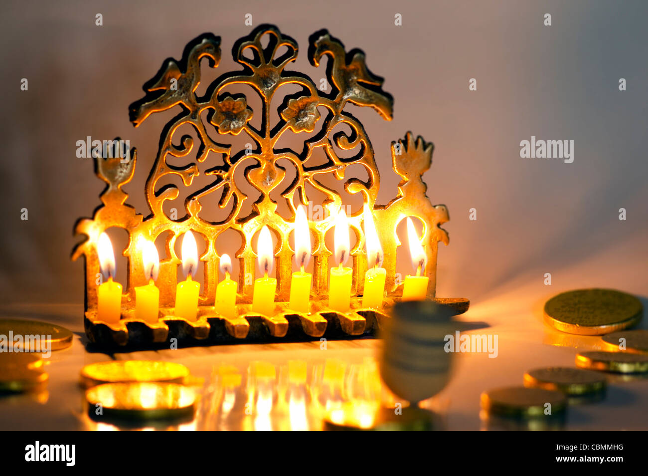 Photo of a dreidel (spinng top), gelts (candy coins) and an ancient brass menorah for the Jewish holiday of Hanukkah. - Stock Image