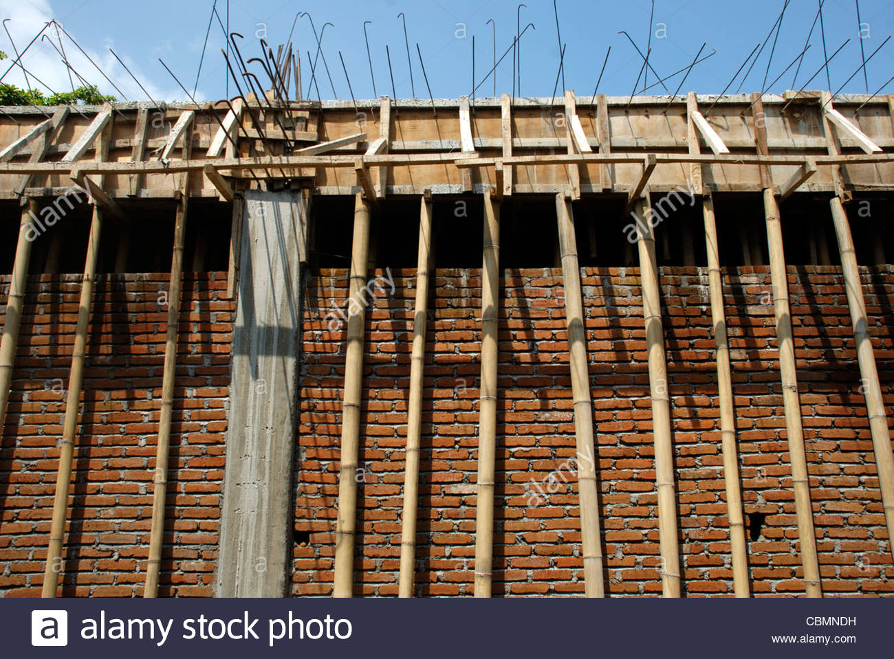 Bamboo poles supporting a newly poured reinforced horizontal beam in building under construction - Stock Image