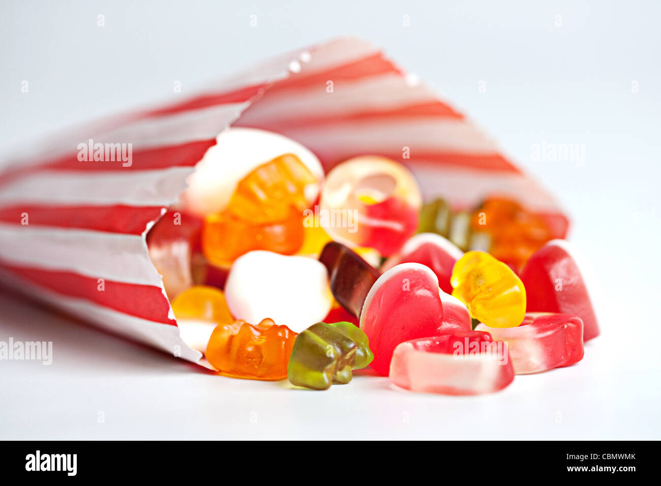 Jelly sweets spilling out of a red and white striped sweetie bag - Stock Image