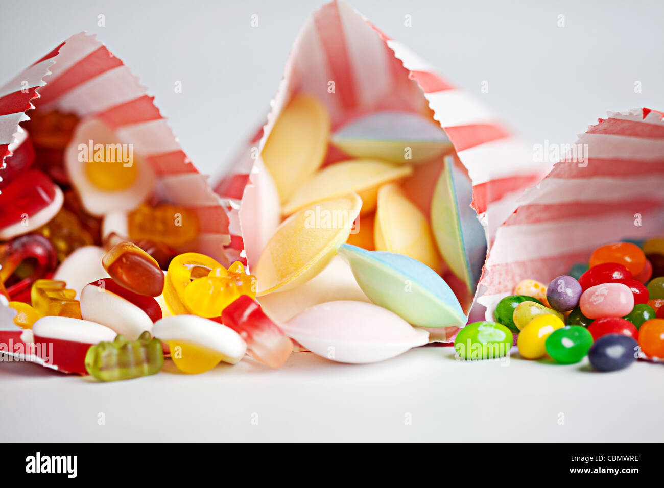 Three red and white striped sweetie bags, each overfloweing with colourful sweets - Stock Image