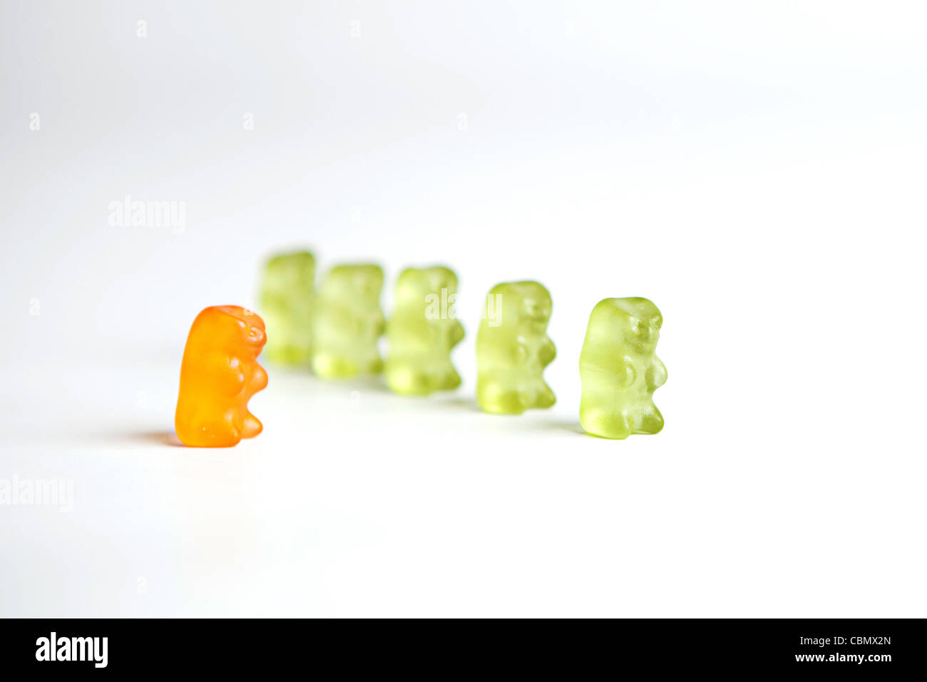 A row a green gummy bears with an 'odd one out' orange bear - Stock Image