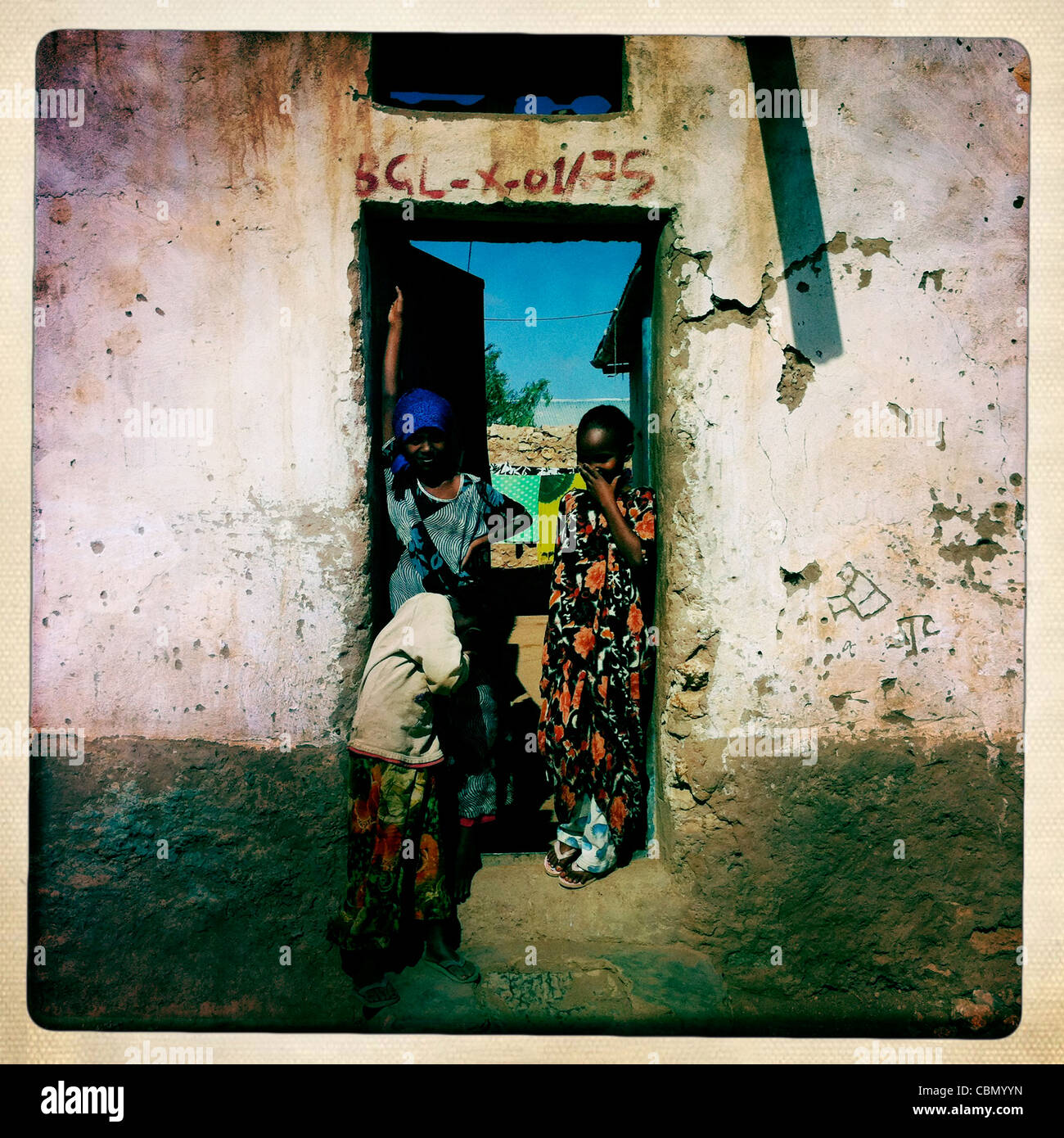 Three Youngsters In The Frame Of A Door Of Decrepit house In Baligubadle Somaliland - Stock Image