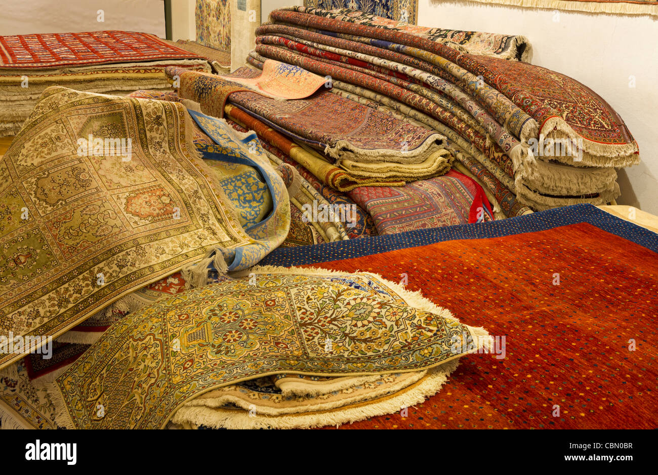 Real oriental carpets lie on a heap sell selling shop sale sellout expensive orient wool silk valuable value color - Stock Image