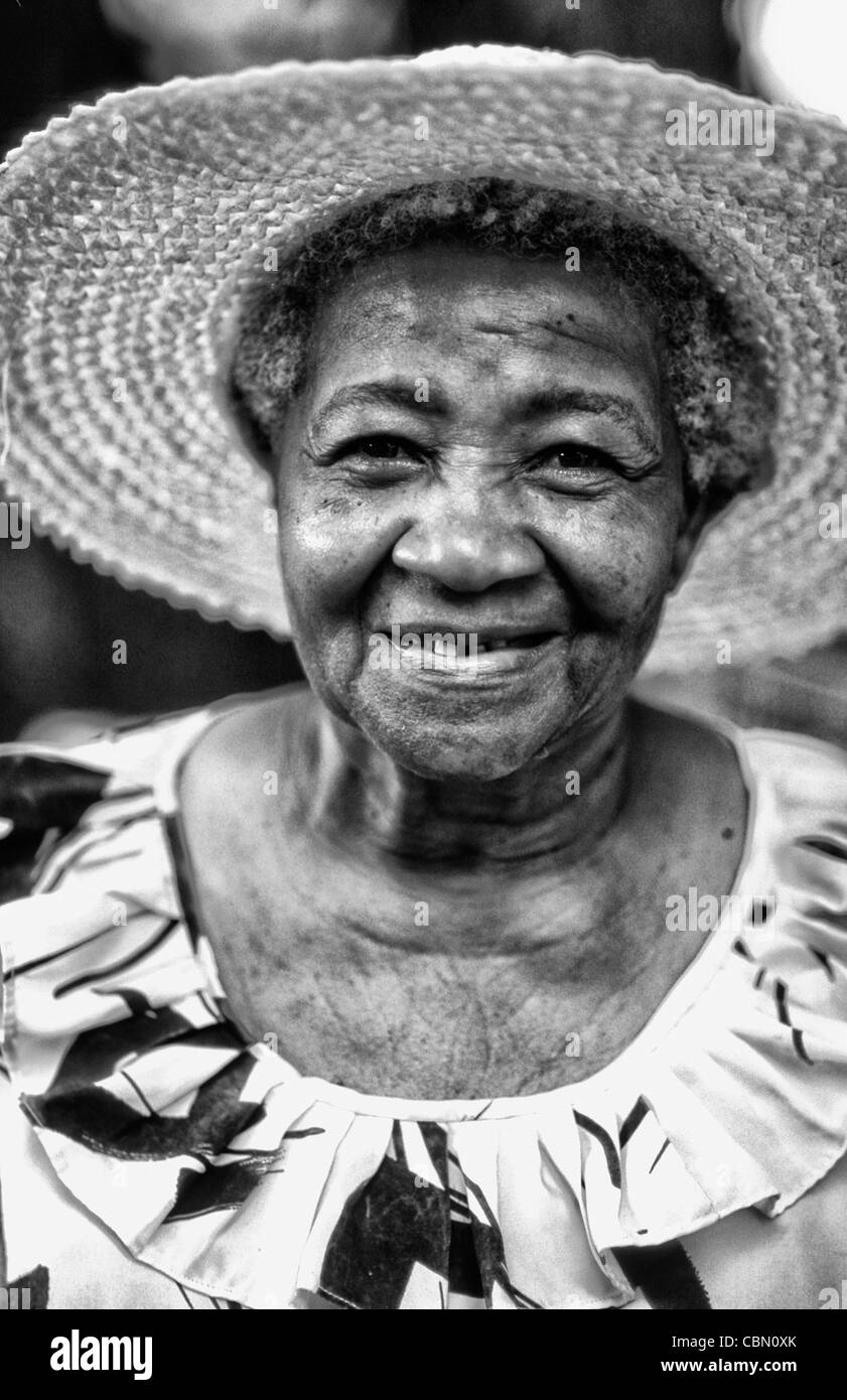 Colorful local woman in hat smiling portrait in the beautiful village of La Digue in the Seychelles Islands off - Stock Image